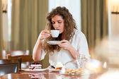 Portré, fiatal, csinos, mosolygós nő élvezi a gyümölcstorta és a kávé kávé / cake shop