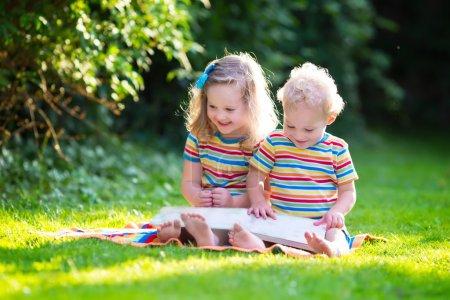 两个孩子在夏天花园里看书