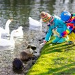 Постер, плакат: Kids feeding otter in autumn park