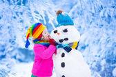 Malá holčička budování muž sněhu v zimě