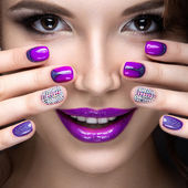 Gyönyörű lány fényes estélyi smink és kabát purple manikűr. Köröm design. Szépség arc