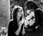 Woman in graveyard giving flowers to the loved one monochrome
