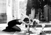 Afflicted woman in grief in front of grave monochrome