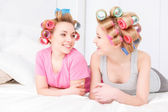 Slumber party. Two young beautiful blond girls wearing pajamas and colorful hair rollers sitting in white bed smiling and looking at each other