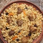 Постер, плакат: Dish of pilaf national uzbek spicy meal with meat rice onion and garlic