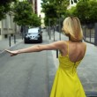 Постер, плакат: Woman in yellow dress hailing a cab taxi