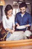 Mladý pár, mytí nádobí v kuchyni