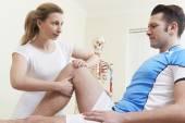 Osteopata nel trattamento di un paziente maschio con infortunio sportivo