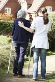 Badante che aiuta donna maggiore a camminare nel giardino utilizzando deambulatore