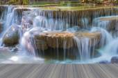 Opening wooden floor, close up of beautiful deep forest water fall on national park