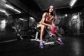 A shaker pózol a padon az edzőteremben fitness lány