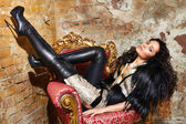 Beautiful sexy woman long brunette hair in black fur Treads on high heel gold pans sitting on the chair red brick wall background makeup fashion style