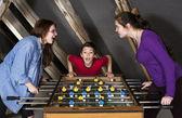 Due ragazze e un ragazzo che gioca un calcio balilla