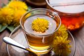 Dandelion tea and honey with yellow blossoms on wooden table, silver spoon,