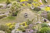 Horní pohled na barevné zahrady s alpských květin, palem, kvetoucích keřů, spáleniny od slunce trávník a okrasné vody dobře dosažitelná kamenné schodiště