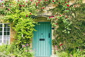 Green wooden doors in an old traditional English stone cottage surrounded by climbing red roses
