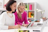 Dvě ženy se dívají na tabletový počítač při práci v kanceláři