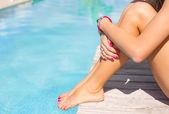 Nő ül a fedélzeten, a medence mellett
