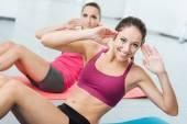 Smiling women exercising at the gym