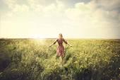 Donna vaga a piedi nella natura verso il sole