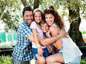 Famiglia felice che abbraccia sotto un albero di olive