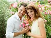 Il ragazzo dà sua donna un fiore in una serra
