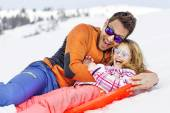 Girl and his father sledding very fast
