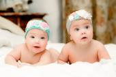 Two twin babies, seven-month girls in nice headbands in bed on white sheets