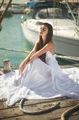 Beautiful, glamorous woman, girl sitting at pier in yacht club n