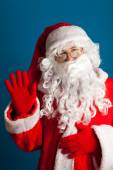 Santa Claus s červeným kostýmu mává rukou