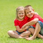 Постер, плакат: Brother and sister on lawn hugging