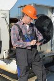 Mladý opravář na střeše, oprava klimatizační systém