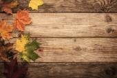 Autumnal maple leaves on the wooden table with filn filter effect background