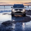 Постер, плакат: Car Mitsubishi Outlander stay on ice coast at winter sunset