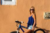 Pretty young hipster blonde girl posing with sport bicycle