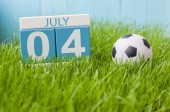 4. července. Obrázek 4. července dřevěný barevný kalendář na zeleném trávníku sněhová vločka. Letní den