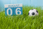 August 6th. Image of august 6 wooden color calendar on green grass lawn background with soccer ball. Summer day. Empty space for text