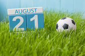 August 21st. Image of august 21 wooden color calendar on green grass lawn background with soccer ball. Summer day. Empty space for text