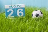 26. srpna. Obrázek od srpna 26 dřevěné barevné kalendáře na zelené trávě trávník pozadí s fotbalovým míčem. Letní den. Prázdné místo pro text