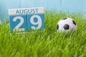 29. srpna. Obrázek ze srpna 29 dřevěné barevné kalendáře na zelené trávě trávník pozadí s fotbalovým míčem. Letní den. Prázdné místo pro text