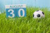 30. srpna. Obrázek ze srpna 30 dřevěný barevný kalendář na zelené trávě trávník pozadí s fotbalovým míčem. Letní den. Prázdné místo pro text