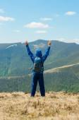 Tourist, man and success in mountains, arms raised. Running, sports, fitness healthy lifestyle outdoors, autumn nature