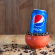 Постер, плакат: Kiev Ukraine April 2015 Can Pepsi cola in a bowl of coffee standing on dark wooden background with empty space Carbonated soft drink that produced and manufactured by PepsiCo Created developed