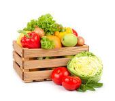 Frisches Gemüse und Obst in einer Holzkiste auf weißem Hintergrund