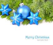 Modrý vánoční koule a hvězdy na větvích vánočního stromku na bílém pozadí. Vánoční pozadí