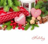 Textilní srdce, ořechy a skořicí poblíž pletené polštáře a větve vánočního stromku na bílém pozadí. Vánoční pozadí