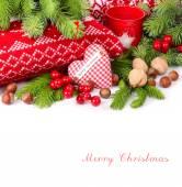 Textile kariert Herz, Nüssen und roten Beeren nahe gestrickte Kissen und Zweige eines Weihnachtsbaumes auf weißem Hintergrund. Weihnachten Hintergrund mit einem Platz für den text
