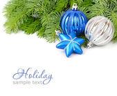 Kék és ezüstös karácsonyi bálok és a bolyhos ága a karácsonyfa, fehér alapon kék csillag. A karácsonyi háttér a hely, a szöveg