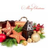 Goldene und rote Weihnachtskugel und Sterne in der Nähe einer kleinen Lampe auf einem weißen Hintergrund. Weihnachten Hintergrund mit einem Platz für den text