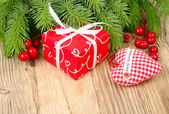 Red gift box, red berries and red checkered textile heart on a wooden background. A Christmas background with a place for the text.